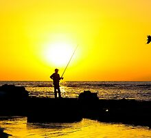 Silhouette of a man fishing on a beach at sunset by PhotoStock-Isra