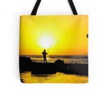 Silhouette of a man fishing on a beach at sunset Tote Bag