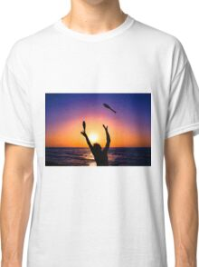 Silhouette of a man juggling on a beach at sunset  Classic T-Shirt