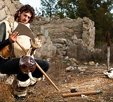 A wild Barbarian Sharpens his war axe  by PhotoStock-Isra