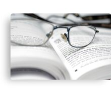reading glasses on an open book with text in Hebrew Canvas Print