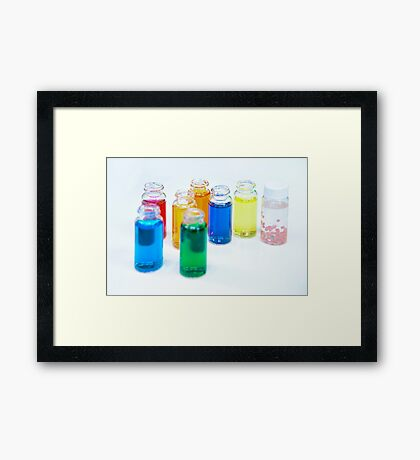 Glass bottles with coloured liquid at a Cosmetics manufacturer Framed Print