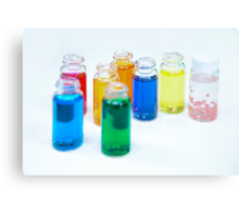 Glass bottles with coloured liquid at a Cosmetics manufacturer Canvas Print
