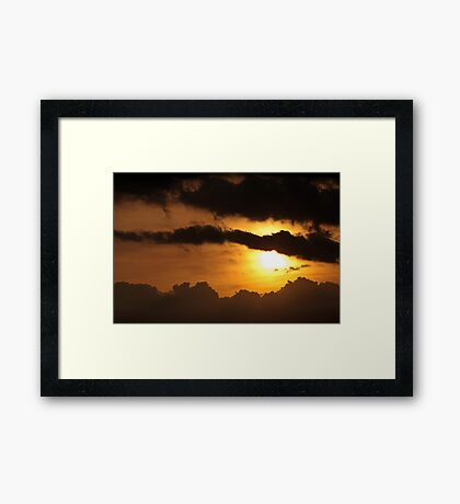 Dramatic sunset with dark clouds Framed Print