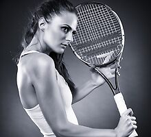 Young female tennis player with racket by naturalis