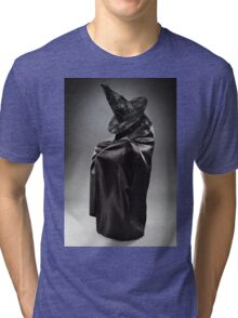 Witch wearing black attire with face hidden Tri-blend T-Shirt