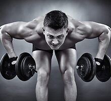 Athletic man working with heavy dumbbells by naturalis