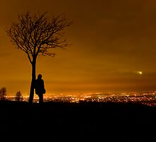 Silhouette of Man Stood By Tree Overlooking Manchester City Centre at Night by Rob Davies