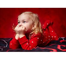Pensive toddler girl laying in bed with hands on chin Photographic Print
