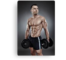 Young athletic man holding two heavy dumbbells Canvas Print