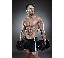 Young athletic man holding two heavy dumbbells Photographic Print