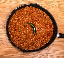Black Pan of Chili with Jalapeno on Wood by dbvirago