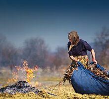 Senior rural woman burning fallen leaves by naturalis