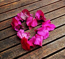 A heart from petals lying on a wooden table by senself