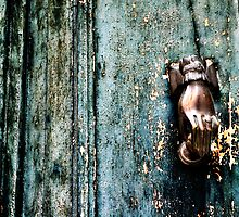 Door knocker on rotting door by Silvia Ganora