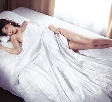 Beautiful young woman sleeping naked in bed covered with white sheets art photo print by ArtNudePhotos