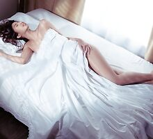 Beautiful woman sleeping naked in bed covered with white sheets lit by sunlight art photo print by ArtNudePhotos
