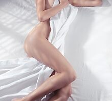 Young woman sleeping naked in bed covering with white sheets art photo print by ArtNudePhotos
