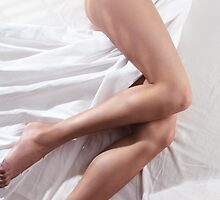 Bare legs of a young woman sleeping naked in bed art photo print by ArtNudePhotos