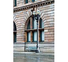 A benach on a city curb Photographic Print