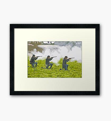 Stylized photo of three Civil War re-enactor soldiers on battlefield firing rifles. Framed Print