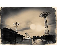 A man walking along the Coney Island boardwalk at sunset with the Parachute Jump in a sepia - colored postcard Photographic Print
