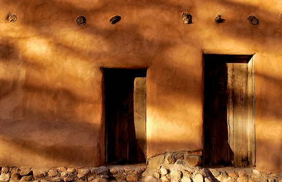 Two wooden doors on an adobe building in Santa Fe New Mexico by Jeff Hathaway