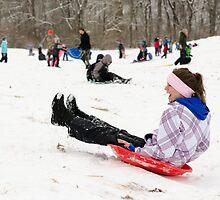 Woman having fun sledding by Mark McElroy