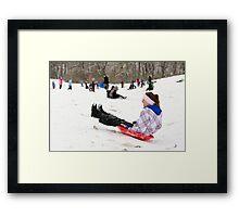 Woman having fun sledding Framed Print