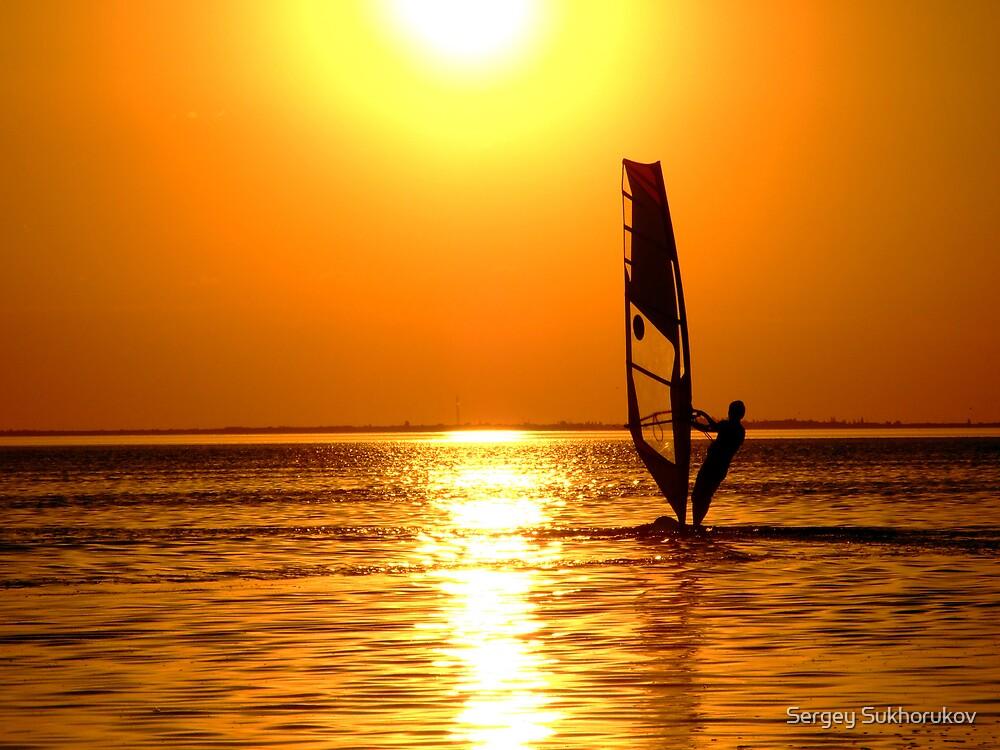 Silhouette of a windsurfer on waves of a gulf on a sunset by Sergey Sukhorukov