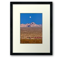 Freight train running across Mojave Desert. Framed Print