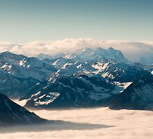 swiss mountains above the clouds in winter by peterwey