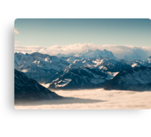 swiss mountains above the clouds in winter Canvas Print