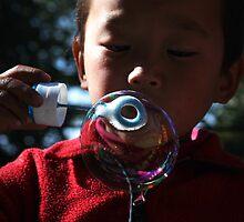 bubble. young tibetan boy, india by tim buckley | bodhiimages