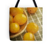 Yellow plum tomatoes on a wooden spoon Tote Bag
