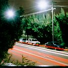 Car lights down a suburban street by yaytractor