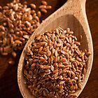 Brown linseeds portion on wooden spoon by Arletta Cwalina