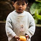 A boy in the rain with an orange by Anthony Begovic