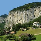 View of cliffs, houses, slopes, greenery and waterfalls on a Swiss cliff by ashishagarwal74