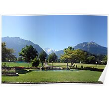 An open field in Interlaken with a view of the mountains in the background Poster