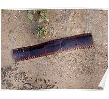 An old abandoned strip of photo film on the ground Poster