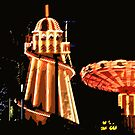 Helter skelter and merry go round at night by Linda More