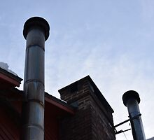 two metal smoke stacks under a blue sky by sbackman