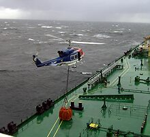 Bell 212 landing stores onto the deck of a supertanker in bad weather by Alasdair