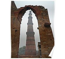 The Qutub Minar framed by remains of a stone wall Poster