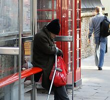 Homeless Man at Bus Stop by Andrew Moughtin-Mumby