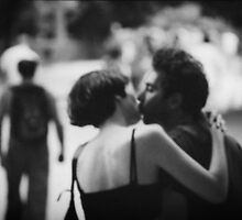 Man and woman kissing in park in black and white analog 35mm film photo by edwardolive