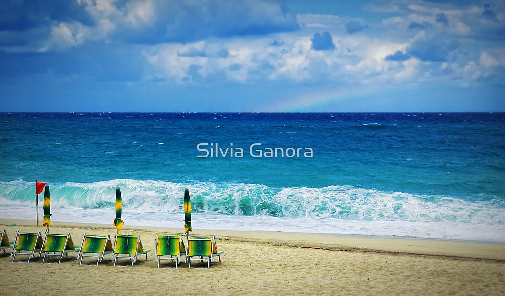 Deck chairs on beach with faraway rainbow by Silvia Ganora