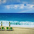 Deck chairs on beach with faraway rainbow by Silvia Ganora