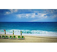 Deck chairs on beach with faraway rainbow Photographic Print
